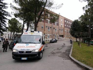 un\' ambulanza e dietro alcune auto parcheggiate all\'interno dell\'ospedale